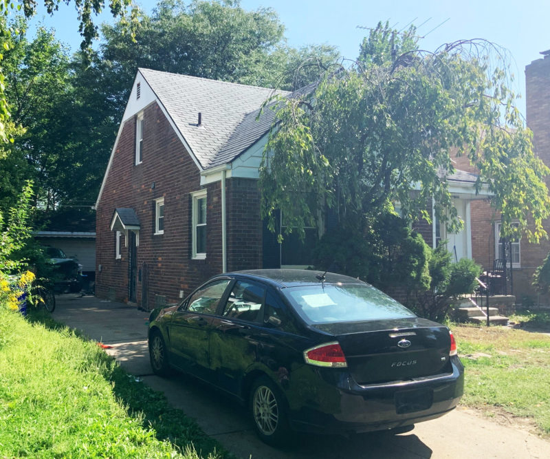 Corner view of a peaked brick home with a black sedan in the driveway