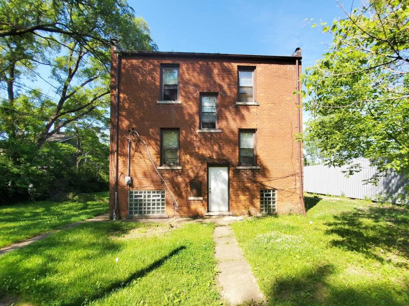 The back of a two-story-plus-basement brick multifamily apartment with a lawn and concrete walkway.