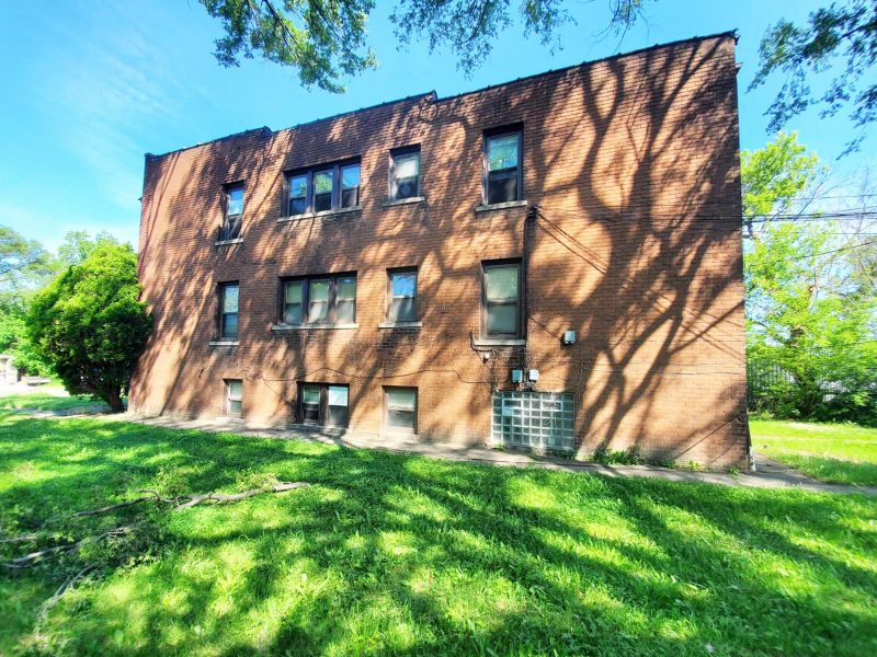 The sun-dappled side of a two-story-plus-basement brick multifamily apartment with a green lawn.