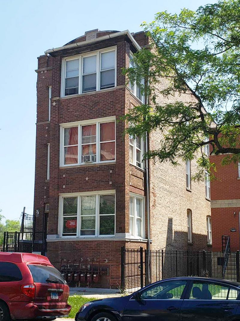 A 3-story brick multifamily apartment building with a tree on the right.
