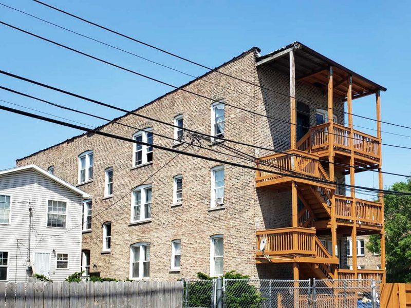 The windowed side of a 3-story brick multifamily apartment building, which a green lot next to it. The wooden stairs at the back of the building are on the right.