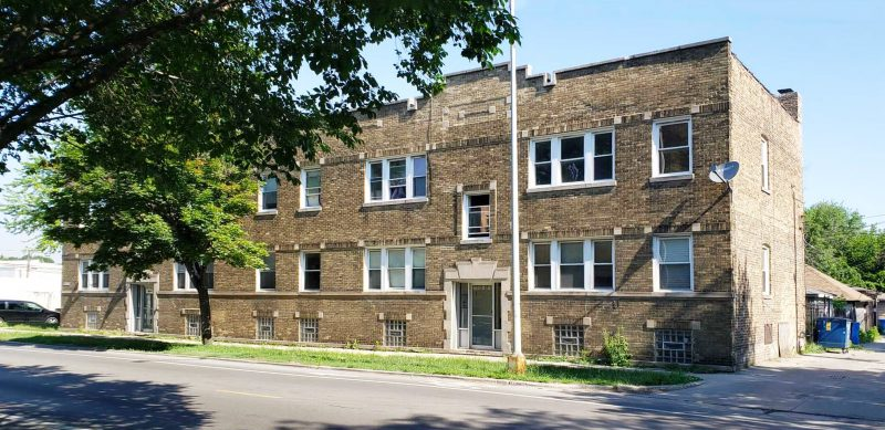 A sunlit two-story brick multifamily apartment building.