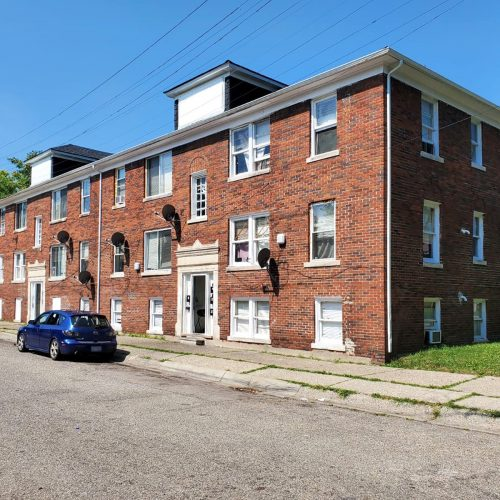 A corner view of a 3-story brick 9-unit apartment buiding with white-trimmed windows and a green lawn on the side.