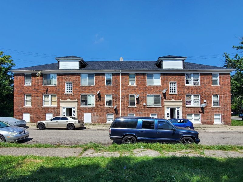 A full-front street view of a 3-story brick 9-unit apartment buiding with white-trimmed windows and a green lawn on the side. Several cars are parked in front.