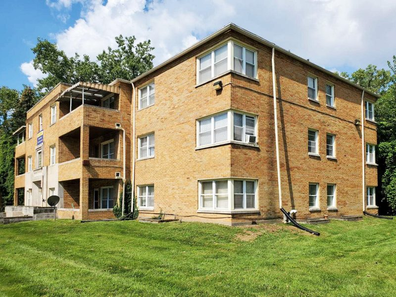 A corner view of a 12-unit multifamily apartment done in tan brick, with a large green lawn in front.