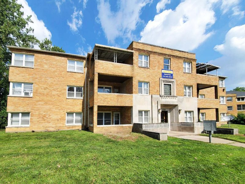 The facade of a 12-unit multifamily apartment done in tan brick, with a large green lawn in front.
