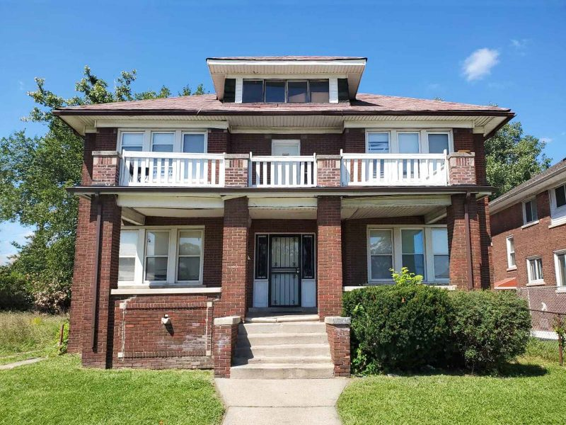 A two-story brick four-unit building with porches on both stories and white trim.