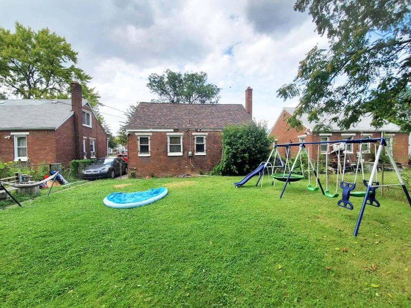 A wide view of the large green lawn behind a brick single-family home, including an empty inflatable pool and a large swingset.
