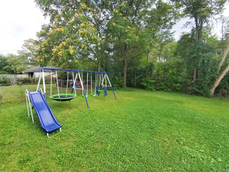 A view of a green lawn with a large swingset on the left side, shaded by deciduous trees.